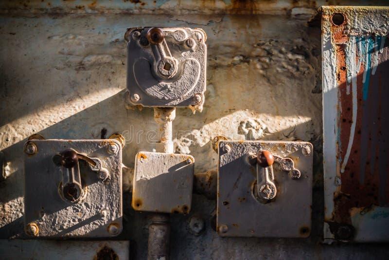 Mycket gammal kontrollantströmbrytare med metallspakhandtaget och elektrisk tråd i det övergav industriella stället arkivfoto