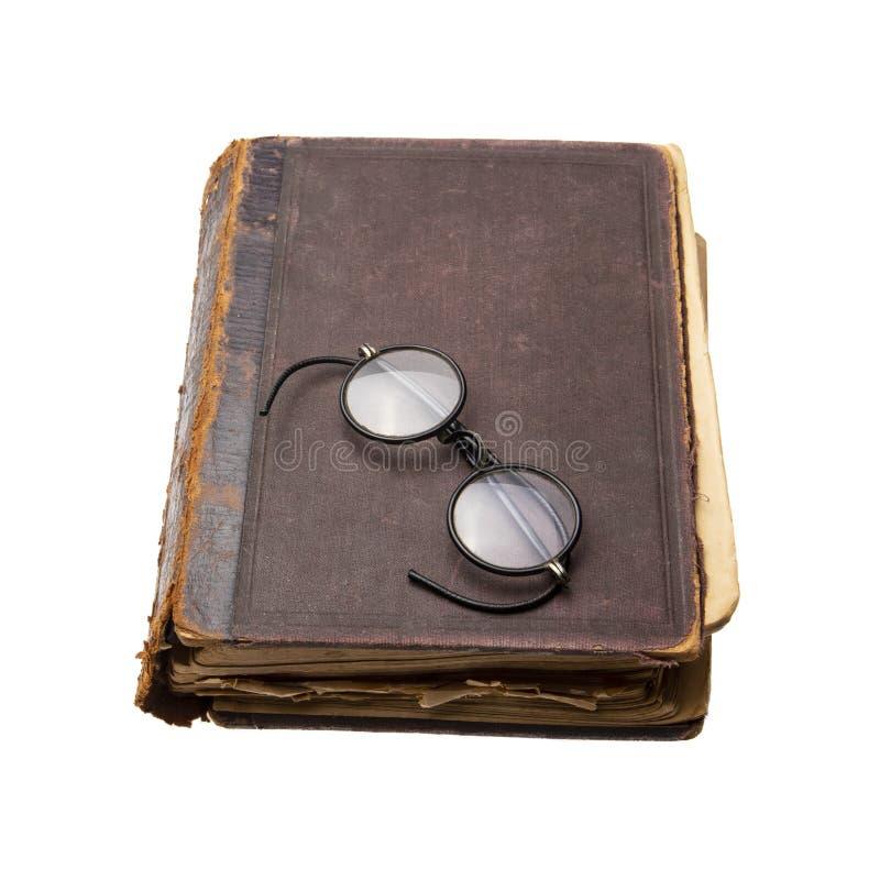 Mycket gammal och sliten bok med antikvitetrundaglasögon isolerat royaltyfria bilder