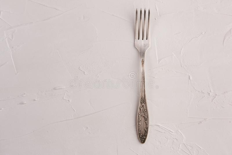 Mycket gammal rostig tappningsilvergaffel som isoleras på en texturbakgrund för vitt cement arkivfoto