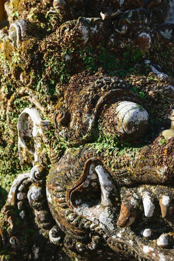 Mycket gammal skulptur för sten för drakehuvudform som täckas med mossa och laver i Bali arkivfoton