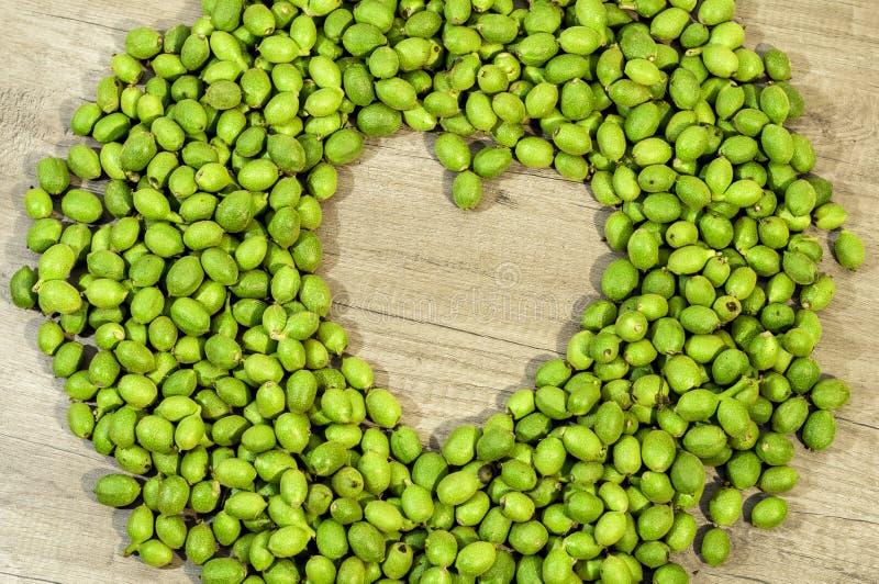 Mycket gröna unga valnötter i skal i formen av hjärta på kitc arkivbilder