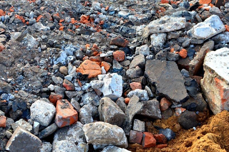 Mycket granitkullersten på jordningen eller den brutna vägen, fragment av tegelstenar, kan användas som en bakgrund eller en text royaltyfri fotografi