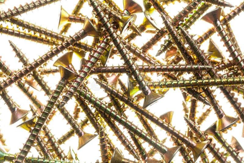 Mycket guld- mässingsskruvar arkivfoton