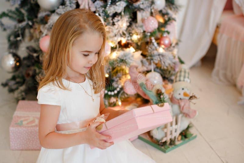 Mycket gullig liten flickablondin i en vit klänning som rymmer en gåvaask arkivfoton