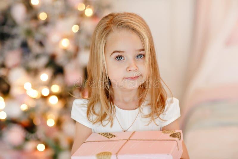 Mycket gullig liten flickablondin i en vit klänning som rymmer en gåvaask royaltyfri foto