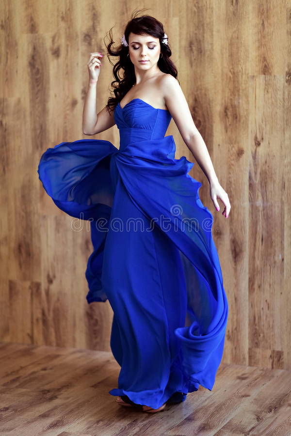 Mycket gullig sinnlig härlig flickabrunett i blå flödande klänning royaltyfri foto