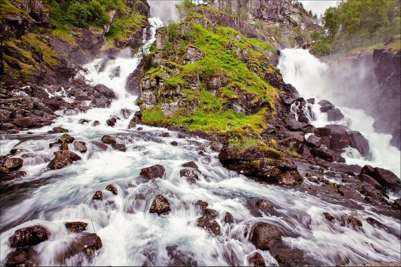 Mycket härlig vattenfall i Norge med snabb-flödande vatten som är stort arkivbilder