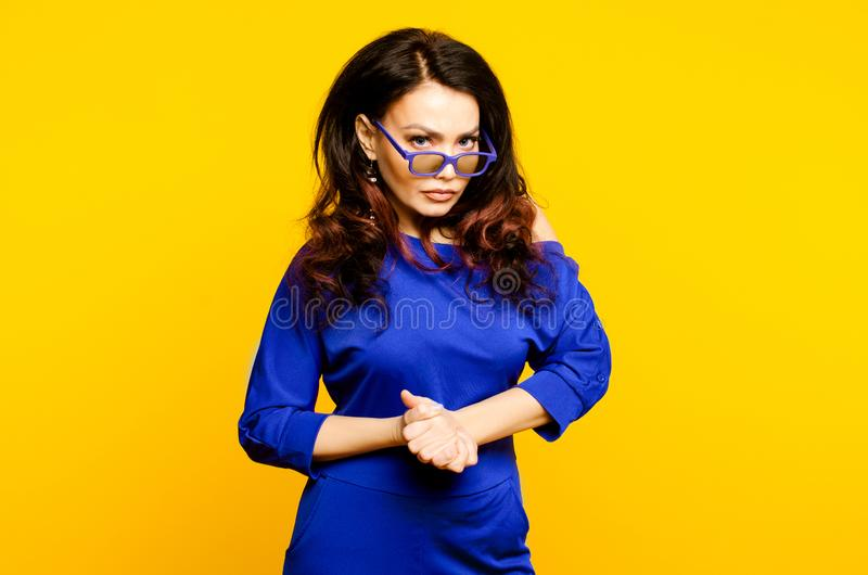 Mycket ilsken affärskvinna i blå dräkt och exponeringsglas som ser till kameran royaltyfri bild