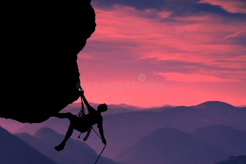 Mycket intressant ?gonblick En ung mountainer har klarat av f?r att kl?ttra till ?verkanten och f?r att uppn? hans m?l royaltyfri fotografi