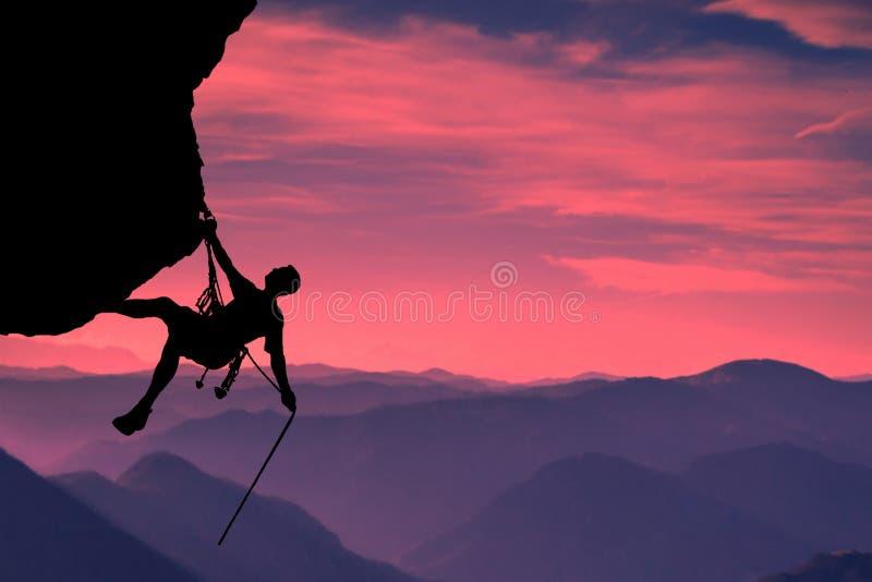 Mycket intressant ?gonblick En ung mountainer har klarat av f?r att kl?ttra till ?verkanten och f?r att uppn? hans m?l royaltyfria foton