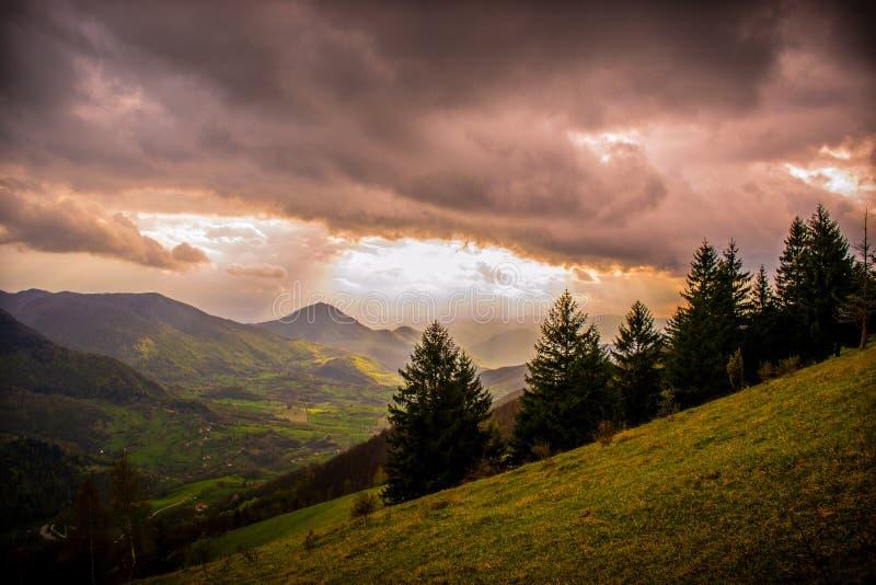 Mycket intressant solnedgång Sikt av vårlandskap, solljus och mörka moln över royaltyfria foton
