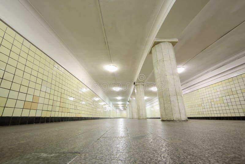 Mycket lång korridor med gulingtegelplattor på väggar, granitgolv royaltyfri foto