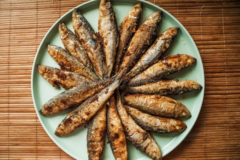 Mycket liten stekt fisk på en stor turkosplatta Salladstek i form av en cirkel ligger, texturen av den färdiga fisken fotografering för bildbyråer