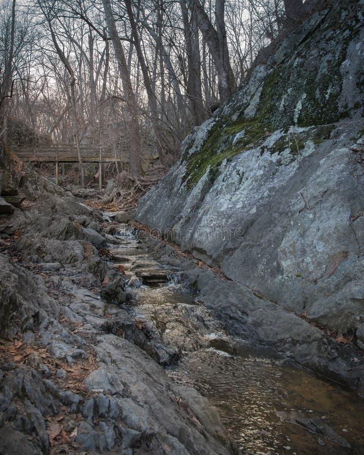 Mycket liten vattenfall nedanför en enkel bro var på kan ta enkla avbrott royaltyfri bild
