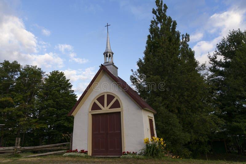 Mycket litet vitt kapell med mörker - röd dörr och tak royaltyfri bild