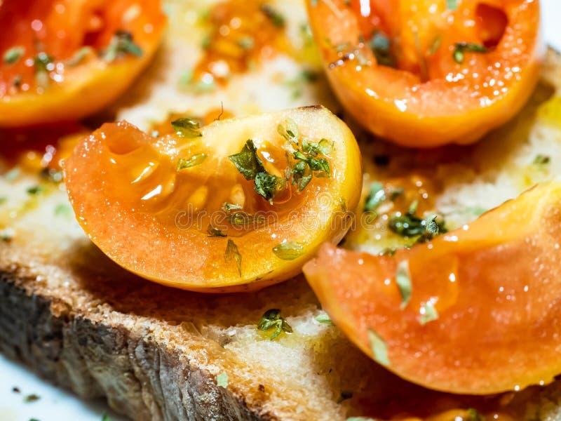 Mycket närbildskott av en grillad bruschetta för italienskt bröd med nya tomater, olivolja arkivbild