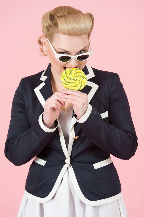 Mycket nätt blond flicka i blått omslag och vitkjol och solglasögon som slickar den gula cirkelklubban över rosa bakgrund arkivbilder