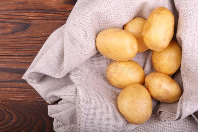 Mycket organiska nya potatisar på ett grått tyg och på en träbakgrund för mörk brunt Sommargrönsaker, bästa sikt arkivfoton