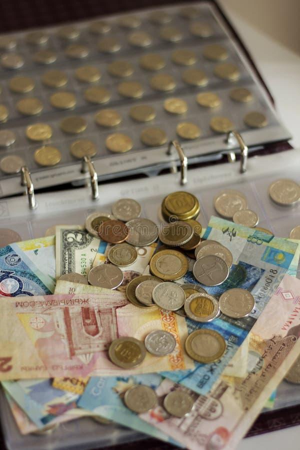 Mycket pappersräkningar och mynt av olika länder på det numismatiska albumet royaltyfria foton