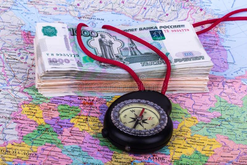 Mycket pengar, en kompass och en översikt arkivbilder