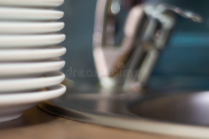 Mycket ren maträtt på tabellen nära vask i kafé closen colors slappt övre siktsvatten för liljan suddighet bakgrund fotografering för bildbyråer