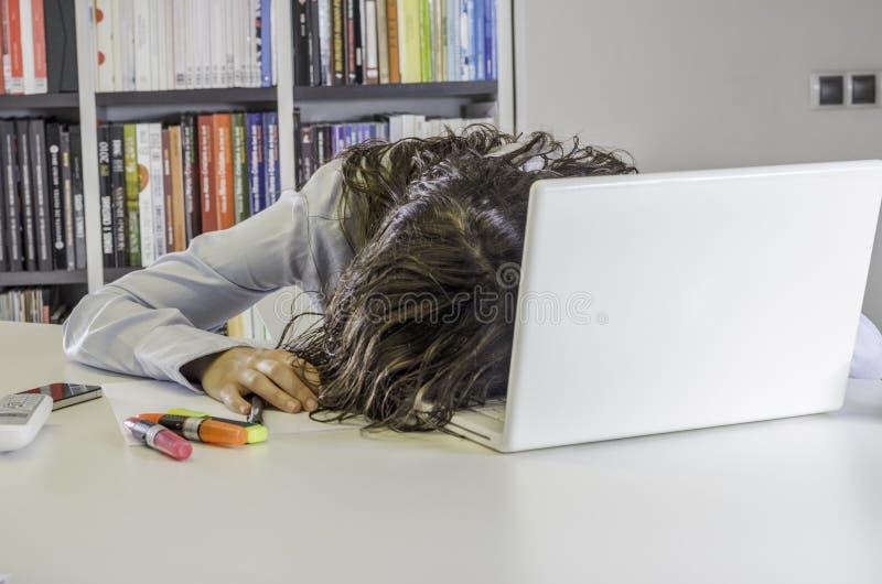 Mycket trött affärskvinna hennes framsida på tangentbordet av bärbara datorn royaltyfria bilder