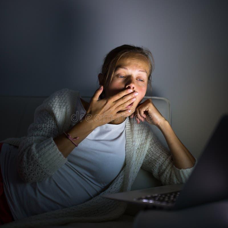 Mycket trött ung kvinna som bränner midnigholjan royaltyfri foto