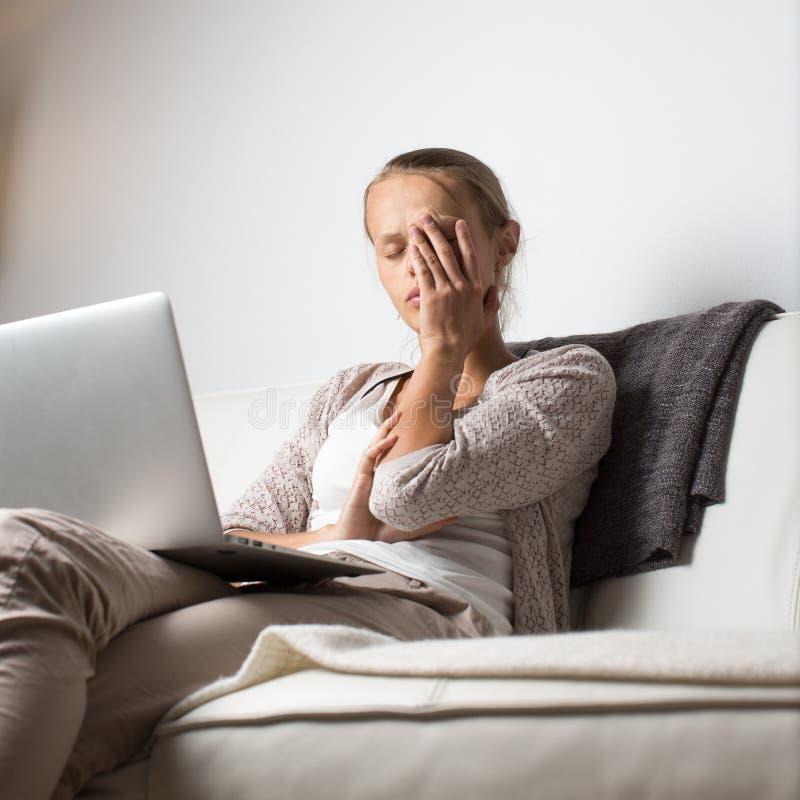 Mycket trött ung kvinna som sent arbetar på natten på hennes bärbar datordator royaltyfria bilder
