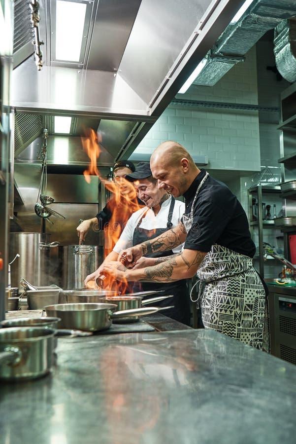Mycket varm gladlynt kock och två hans assistenter som förbereder maträtten på ugnen med en öppen brand i köket av arkivbilder
