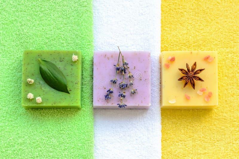 Mydło zielone ziołowe, fioletowy lawenda jeden i jeszcze jeden żółty z ziołami i solą himalajską na zielonych, białych i żółtych  zdjęcia royalty free