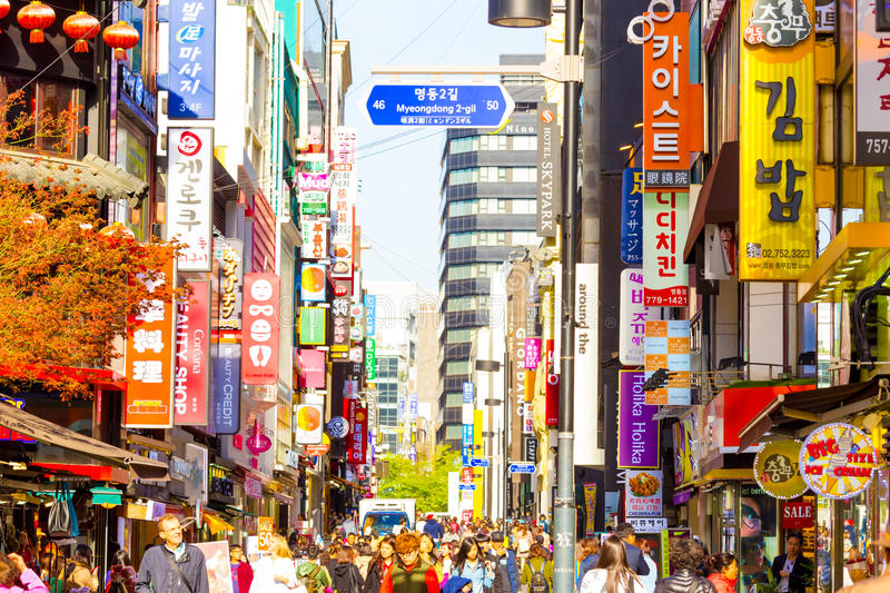 Myeongdong Crowded Shopping Street Stores Signs H. Seoul, South Korea - April 17, 2015: People walking down bustling Myeongdong pedestrian shopping street stock photos