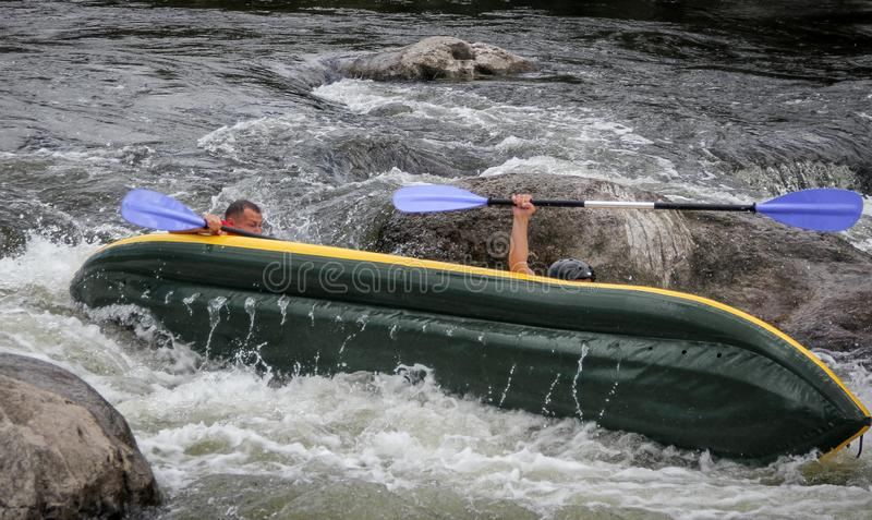 Myhiya / Ukraine - August 24 2018: Kayakers fights the white water in a Pivdenny Bug river. They and their kayak are flipping over. In the the wild water stock photography