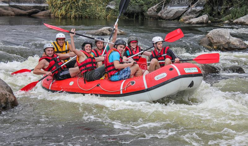 Myhiya / Ukraine - June 24 2018: Group of happy people with guide whitewater rafting and rowing on river,  extreme and fun sport. At tourist attraction. Rafting stock image
