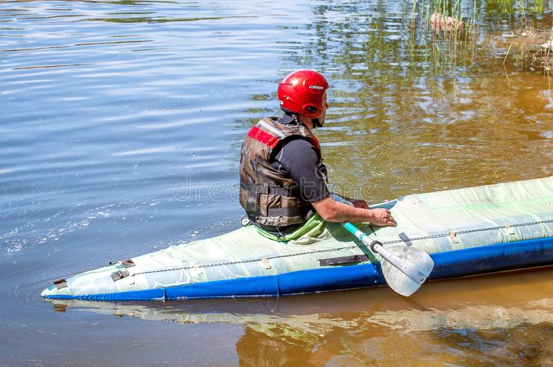 Rafting and kayaking. An athlete in sports equipment sits in a rubber inflatable boat. Extreme. Ecological water tourism stock photography