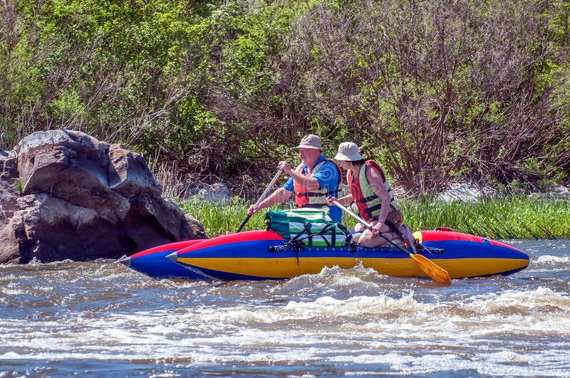 Rafting and kayaking. A man and a woman in old age are sailing on a rubber inflatable boat. Water splashes close-up. royalty free stock image