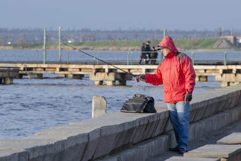 Mykolaiv, Украина - 25-ое марта 2017: Рыболов в красной куртке улавливает рыб на пристани стоковое изображение