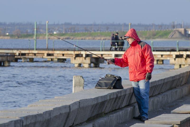 Mykolaiv, de Oekraïne - Maart 25, 2017: Visser in een rode vis van jasjevangsten op de pijler stock afbeelding