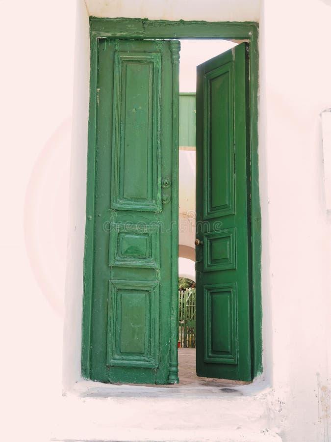 Mykonos ö Grekland, halvöppen grön dörr av det kalkade huset royaltyfria foton
