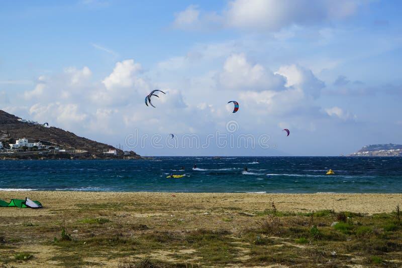Mykonos, Греция - 28-ое сентября 2017: Kitesurfing, вид крайности windsurf водные виды спорта восхождения на борт плавания в силь стоковые фотографии rf