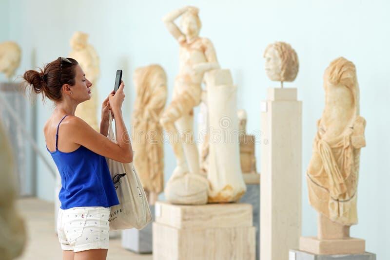 Mykonos, Grecia, el 11 de septiembre de 2018, un turista toma las fotografías en el museo arqueológico foto de archivo