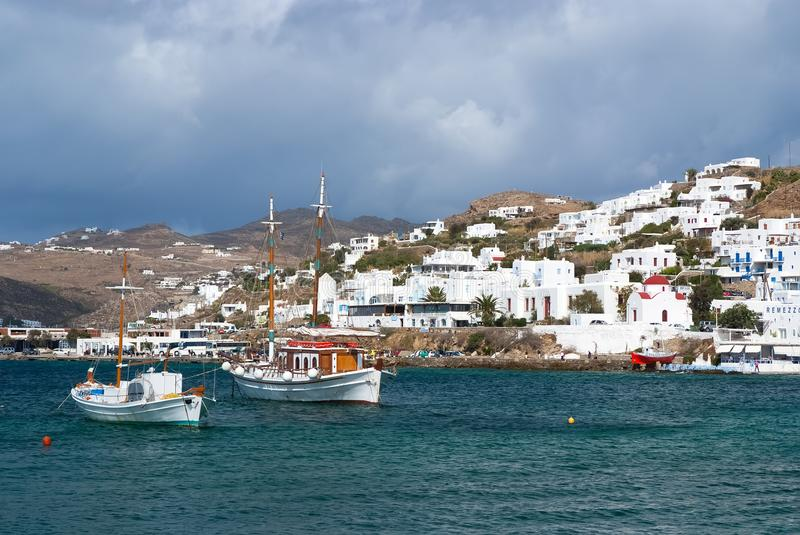 Mykonos, Greece - May 04, 2010: Fishing village at seaside on cloudy sky. Houses at sea coast. Boats in blue sea on royalty free stock photography