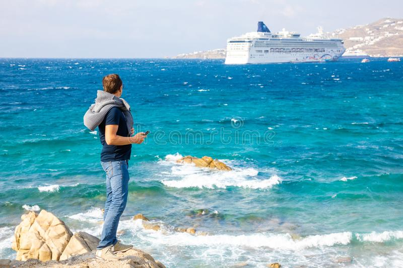 Mykonos, Greece - 17.10.2018: Young man looking on cruise ship, vacation at the colorfull town of Mikonos, Greece stock images