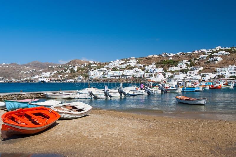 Mykonos Grekland - Maj 04, 2010: fartyg på havsstranden By med vithus på det blåa havet på berglandskap Sommar arkivbild