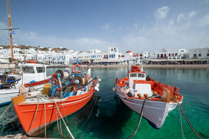 Harbor of Aegean sea, Mykonos island. Greece. Mykonos town panorama with Greek Orthodox church. Traditional white buildings on embankment and boats on quay stock photo