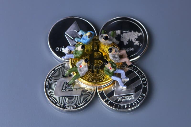 Mynt av olika crypto-valutor med statyettfolk som sitter på dem Bitcoin streck, krusning, ethereum, litecoin royaltyfri foto
