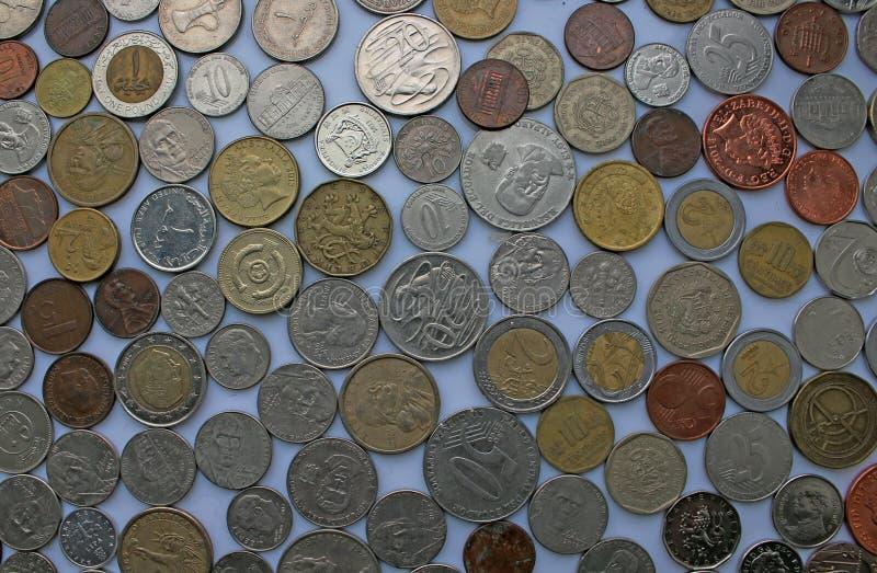 Mynt av olika valutor som lägger bredvid de - euroet, bad, dollar, pund och mer royaltyfria foton