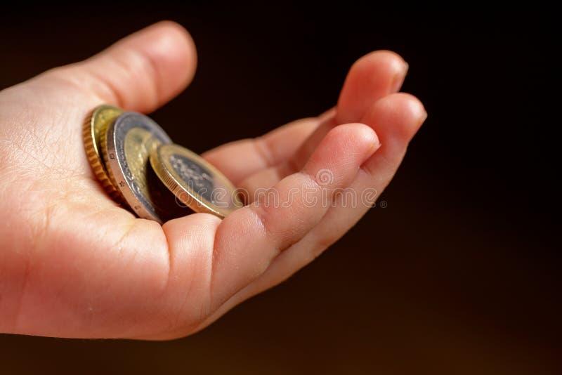Mynt för barninnehaveuro i hans hand Fickpengar lagerför bild Fattig grupp för låg inkomst Stranda av hår vänder mot in - Bild cl royaltyfria bilder