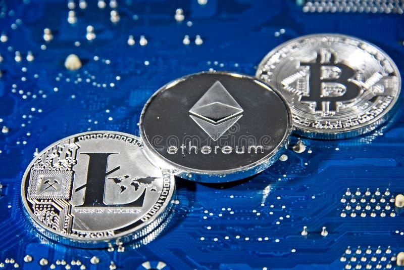 Mynt för BTC LTC ETH Bitcoin Litecoin Ethereum på strömkretsbräde royaltyfri fotografi