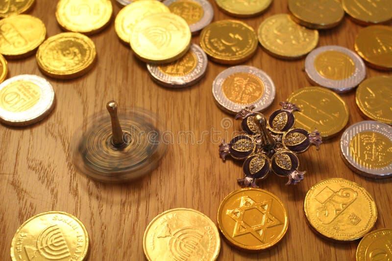 Mynt för Chanukkahgeltchoklad med stjärnan av David på baksida- och silversnurrdreidel med granatäpplet royaltyfria bilder