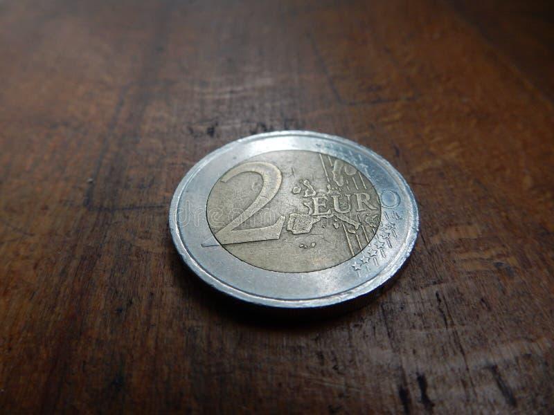mynt för euro 2 på gammal trätabellbakgrund fotografering för bildbyråer